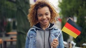 alemão : Slow motion portrait of happy African American woman smiling, holding German flag and looking at camera, bright flag is flutteting in the wind.