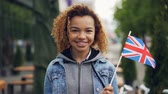 estrangeiro : Slowmotion portrait of young and pretty African American lady holding British flag and smiling looking at camera on windy day. Glad tourist and attractive people concept. Vídeos
