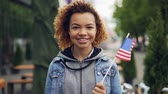 estrangeiro : Slow motion portrait of pretty African American girl teenager looking at camera and holding US flag standing outside in modern city. Tourism and people concept. Vídeos