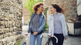 estrangeiro : Slowmotion of happy Caucasian and African American girls tourists laughing and walking with bicycles along street with old buildings. Tourism and people concept.