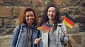 nevetés : Slowmotion portrait of happy students in Germany pretty girls waving German flags and laughing looking at camera. Friendship, tourism and happy people concept.