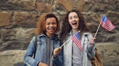 estrangeiro : Slow motion portrait of two friends young women in casual clothes waving American flags and laughing looking at camera. Friendship, tourism and happy people concept.