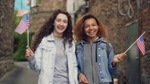 tifose : Slowmotion portrait of two pretty girls in casual clothing waving American flags and laughing looking at camera. Friendship, tourism and happy people concept.