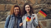 alemão : Slowmotion portrait of two smiling girls friends waving German flags and looking at camera standing against stone wall. Friendship, tourism and happy people concept.
