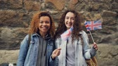 nevetés : Slowmotion portrait of two female friends foreign students in the UK waving British flags and laughing looking at camera. Friendship, tourism and happy people concept.