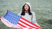 oficial : Slow motion portrait of happy American girl holding United States flag and moving it standing on the sea coast with waves visible. Nationality and countries concept.