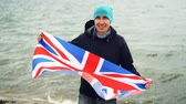 língua : Slow motion portrait of patriotic Englishman holding flag of Great Britain standing on sea coast and smiling happily. Proud citizens, foreign countries and people concept.