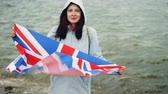 estrangeiro : Slow motion portrait of glad tourist visiting Great Britain holding British national flag and smiling standing on sea shore with beautiful nature visible. Vídeos
