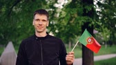 Португалия : Slow motion portrait of cheerful young man proud patriot waving Portuguese flag and smiling standing in city park with high trees and beautiful lawns. People and countries concept.