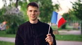 размахивание : Slow motion portrait of Frenchman waving national flag looking at camera and smiling with beautiful modern park in background. People, countries and nature concept.