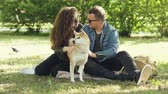tur : Husband and wife happy couple are fussing their pet shiba inu puppy sitting on grass in park and talking. Conversation, animals and modern lifestyle concept.