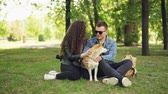 tur : Attractive girl and her boyfriend loving dog owners are patting their pet and talking resting in the park at weekend. Happiness, nature and people concept.