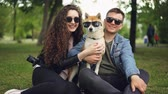 shiba : Portrait of cute couple and shiba inu dog all wearing sunglasses looking at camera and smiling sitting on grass in park. Modern lifestyle, cute animals and nature concept.
