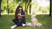 shiba : Attractive young woman is reading book sitting on grass in park while her well-bred dog is sitting near her owner and looking around. Leisure and animals concept.