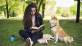 shiba : Pretty young lady is reading book in the park and patting cute dog shiba inu breed, well-bred pet is sitting on the grass near its owner. Animals and people concept.