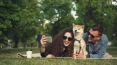 eğlenceli : Young woman is taking selfie in the park lying on grass with her boyfriend and pet dog, adorable animal is sneezing and licking its nose, people are laughing.