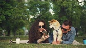 proprietaire : Young woman is showing funny pictures on smartphone to her boyfriend while relaxing in park with pet dog, people are lying on plaid on grass and watching screen.