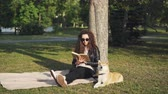 čtenář : Attractive girl student is reading book sitting on plaid under tree in city park with her puppy lying near and enjoying sunlight. Hobby, leisure and animals concept.