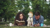 shiba : Happy couple is resting in park, man is using smartphone while woman is reading book, their dog is sitting between them on blanket. People are talking and smiling.