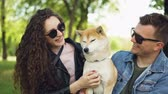 tur : Slow motion of happy couple kissing beautiful dog, laughing and talking sitting on grass in park enjoying summertime. Loving animals, relationship and leisure concept.