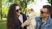 tur : Slow motion of two people caring dog owners kissing and patting adorable pedigree pet sitting on grass in park in city. Love, relationship and nature concept. Stok Video