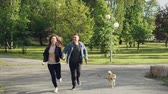 en couple : Slow motion of young married couple running in the park with small dog enjoying freedom and activity with beautiful green trees and grass around them.