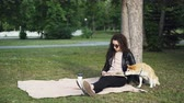 shiba inu : Relaxed girl is reading book and drinking takeaway coffee sitting on lawn in park while her cute dog is smelling ground and air sitting under tree. Leisure and pets concept. Stock Footage