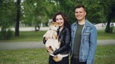 orgulho : Slow motion portrait of attractive young woman brunette holding her dog standing in the park with boyfriend. Happy people are looking at camera and smiling.