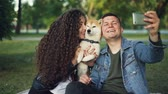cachorro : Slow motion of happy pair girl and guy taking selfie with cute dog posing and kissing animal holding smartphone. Modern technology, parks and leisure concept. Vídeos