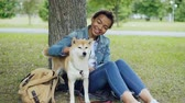 prazer : Pretty mixed race girl is petting cute shiba inu dog and talking to it with tenderness resting in park at weekend. Friendship between humans and animals concept. Stock Footage