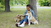 lovable : Pretty African American girl student is reading book sitting in park on lawn while her well-bred dog is sitting near her and smelling air and looking around.