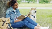 lovable : Kind mixed race woman is reading book in park and stroking her dog sitting on lawn under tree together. Intelligent hobby, caressing animals and youth concept. Stock Footage