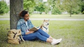 prato : Young African American lady is reading book sitting on lawn in park and stroking her purebred pet dog with love and tenderness. Enjoying weekend with animals concept.