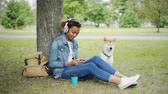 shiba : Modern African American girl is listening to music with headphones and using smartphone relaxing in city park with pet dog, stroking and caressing the animal.