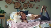 orgulho : Happy African American girl proud dog owner is taking selfie with cute pet lying on bed in modern apartment using smartphone. Technology and social media concept.