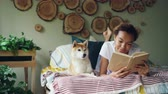 prazer : Smiling African American student lovely girl is reading book on bed at home while her pet dog is lying near her. Hobby, leisure, animals and interior concept.