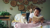 prazer : Cheerful mixed race teenage girl is reading book enjoying literature then stroking her shiba inu dog lying on bed near her. Hobby, modern lifestyle and animals concept.