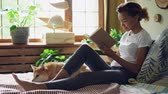 shiba : Pretty girl mixed race student is reading book and caressing pet dog expressing love and care sitting on bed in the house. Youth, hobby and animals concept. Stock Footage