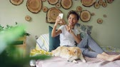 shiba : Happy African American teenager is making video call with smartphone calling friends talking and gesturing while her cute dog is lying on bed with her. Stock Footage