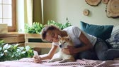 shiba : Pretty girl proud dog owner is making video call and caressing her purebred dog lying on bed at home, young woman is talking and showing animal to interlocutor. Stock Footage
