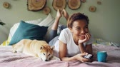 empurrando : African American woman is watching TV holding remote control pressing buttons and laughing while her pet dog is lying beside her. Entertainment and technology concept.