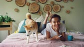 shiba inu : Cheerful mixed race student is watching TV holding remote and pressing buttons choosing television channels while her dog is moving on bed at home.