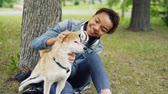 ternura : Slow motion of happy dog owner attractive young woman caressing cute shiba inu dog fussing its fur and looking at it with tenderness resting in park in summer. Archivo de Video