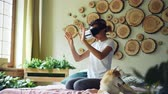 shiba : African American girl is using virtual reality glasses sitting on bed at home, she is moving hands and head and smiling while her cute dog is yawning and licking its muzzle.