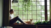читатель : Attractive young lady is reading book sitting on windowsill in the house together with adorable puppy. Large window, green plants, nice interior is visible. Стоковые видеозаписи