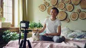 sobre : Cheerful African American woman popular blogger recording video for her online blog about shiba inu dogs using camera on tripod. Girl is sitting on bed with her pet.