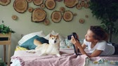 hrdý : Proud dog owner is taking pictures of her pedigree dog using professional camera lying on bed at home. Beautiful furniture, cute animal and green plants are visible.