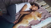 relation de confiance : High angle view of pretty young woman in pajamas and her adorable puppy sleeping together on bed at home. Friendship, rest and furniture concept.