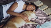 shiba inu : Beautiful African American teenager and adorable pet dog are sleeping together on wooden bed, girl is wearing comfortable pajamas and hugging animal.