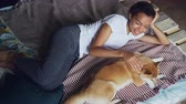 shiba : Kind African American girl is stroking lovely pet dog lying on bed at home together, enjoying rest and tranquility. Modern wooden bed and bright linen is visible.